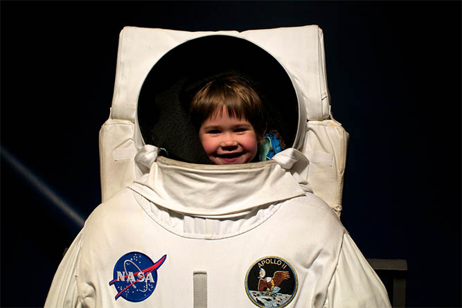 The author's daughter enjoying a summer adventure at a space center.